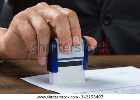 Cropped image of businessman stamping document at desk - stock photo
