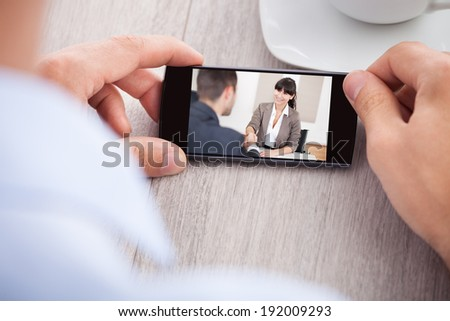 Cropped image of businessman watching movie at table in office - stock photo