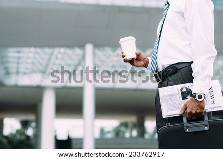 Cropped image of businessman with coffee and newspaper standing outside office building - stock photo