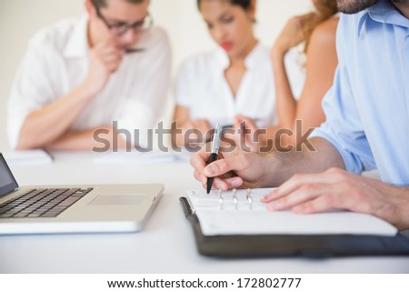 Cropped image of businessman writing in diary in office meeting - stock photo