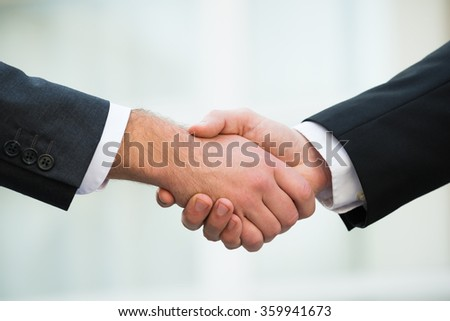 Cropped image of businessmen shaking hands outdoors - stock photo