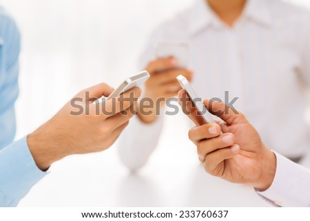 Cropped image of businessmen text messaging - stock photo