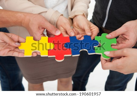Cropped image of businesspeople joining puzzle pieces in office - stock photo