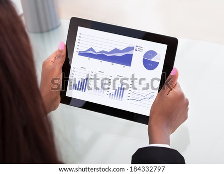 Cropped image of businesswoman analyzing financial charts on digital tablet at desk in office - stock photo