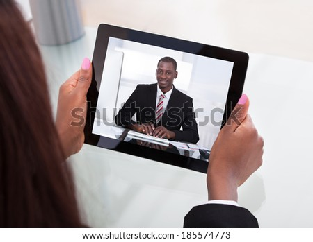 Cropped image of businesswoman attending video conference with colleague on digital tablet at desk in office - stock photo