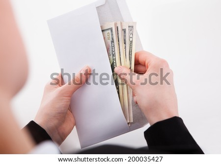Cropped image of businesswoman putting American banknotes in envelope at office - stock photo