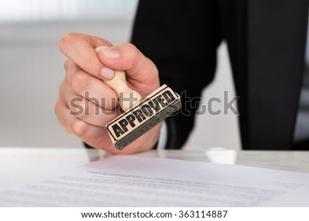 Cropped image of businesswoman stamping approved on contract paper at desk in office - stock photo