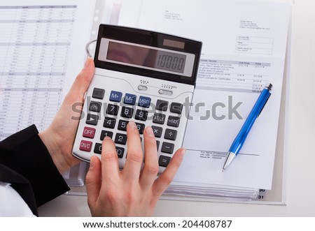 Cropped image of businesswoman using calculator while working at office desk - stock photo
