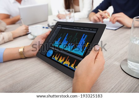 Cropped image of businesswoman using digital tablet at desk in office - stock photo