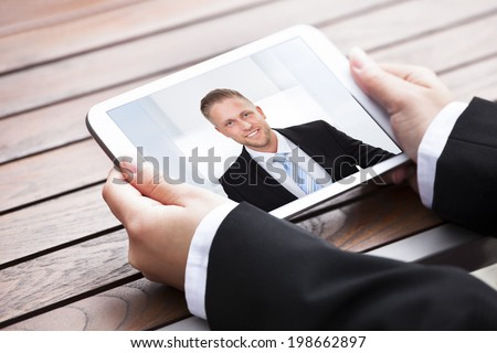 Cropped image of businesswoman video conferencing with colleague on digital tablet outdoors - stock photo