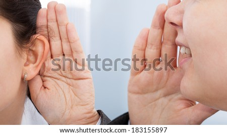 Cropped image of businesswoman whispering in colleagues ear - stock photo
