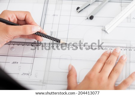 Cropped image of businesswoman working on blueprint at office - stock photo