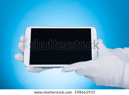 Cropped image of butler showing digital tablet over blue background - stock photo
