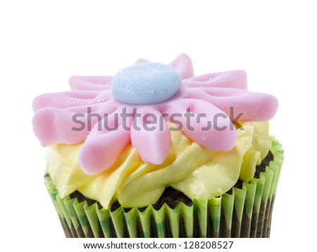 Cropped image of chocolate flavor cupcake with creamy icing and flower candy on top - stock photo