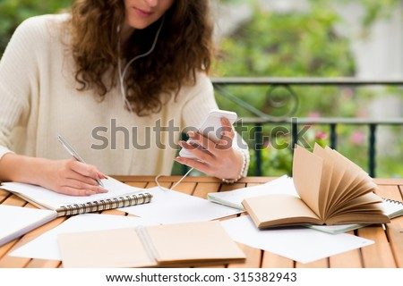Cropped image of copywriter listening to the music on her phone while working - stock photo
