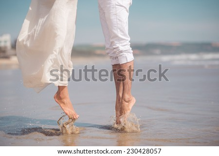 Cropped image of couple jumping on the beach - stock photo