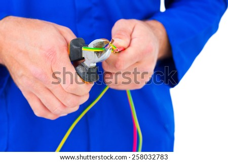 Cropped image of electrician cutting wire with pliers over white background - stock photo