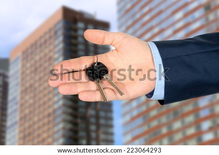 Cropped image of estate agent giving house keys  outside. Modern buildings beside - stock photo