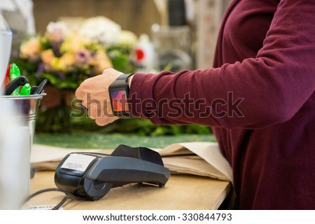 Cropped image of female customer paying through smart watch at flower shop - stock photo