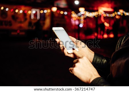 Cropped image of female hands holding mobile cell phone with blank copy space screen on a night city background. bokeh - stock photo
