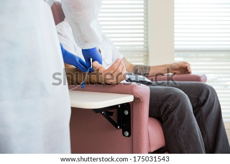 Cropped image of female nurse adjusting IV drip on patient's hand in chemo room - stock photo