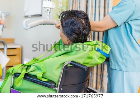 Cropped image of female nurse holding hydraulic lift's handle with patient on wheelchair in hospital - stock photo