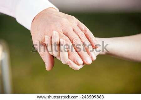 Cropped image of female nurse holding senior man's hand - stock photo