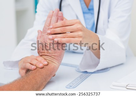 Cropped image of female physiotherapist examining male patients wrist in clinic - stock photo