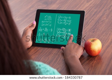 Cropped image of female student solving math problems on digital tablet at classroom desk - stock photo