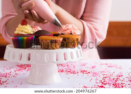 Cropped image of girl decorating cupcakes - stock photo