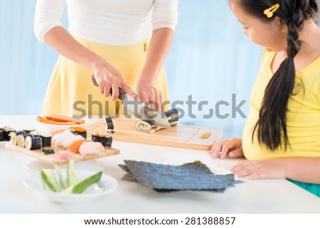 Cropped image of girl looking how her mother is making sushi - stock photo