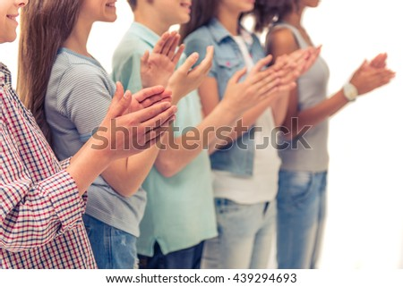 Cropped image of group of teenage boys and girls clapping hands, standing in a row, isolated on white - stock photo