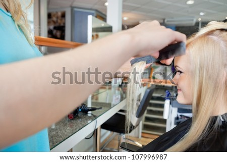 Cropped image of hairstylist combing hair of young female customer before haircut at salon - stock photo