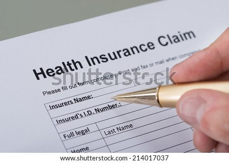 Cropped image of hand filling health insurance form on desk - stock photo