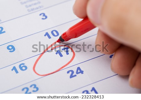 Cropped image of hand marking 17th date on calendar - stock photo