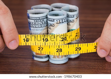 Cropped image of hands holding banknote with measure tape on desk - stock photo