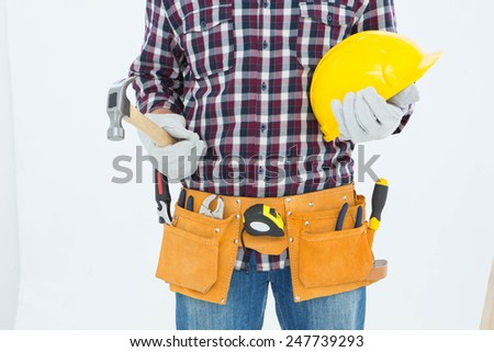 Cropped image of handyman wearing tool belt while holding hard hat and hammer on white background - stock photo