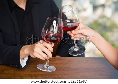 Cropped image of human hands toasting with glasses of red wine  - stock photo