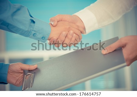 Cropped image of human handshaking after signing a contract on the foreground  - stock photo