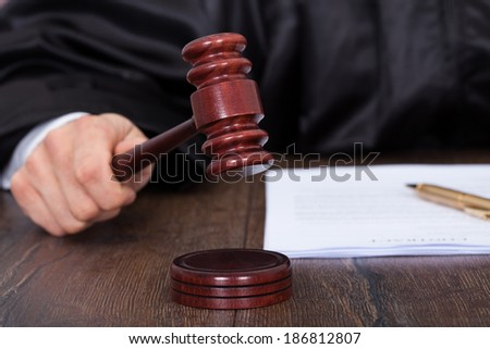 Cropped image of judge giving verdict by hitting mallet at desk - stock photo