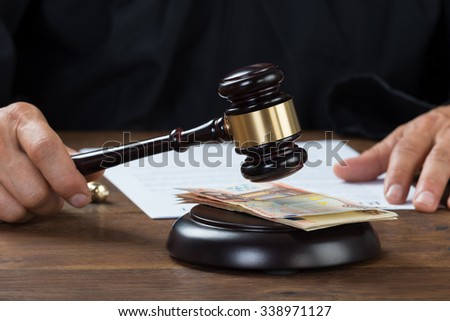 Cropped image of judge holding gavel over banknotes at desk - stock photo