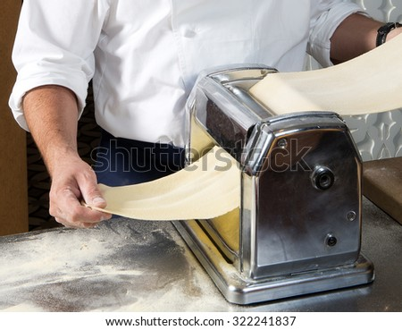 Cropped image of male chef processing  pasta sheet in machine at kitchen - stock photo