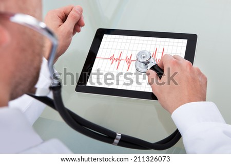 Cropped image of male doctor analyzing heartbeat on digital tablet through stethoscope - stock photo