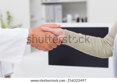Cropped image of male doctor and female patient shaking hands in clinic - stock photo