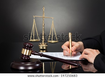 Cropped image of male judge signing document at desk against black background - stock photo
