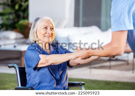 Cropped image of male nurse helping senior woman to get up from wheelchair at nursing home - stock photo