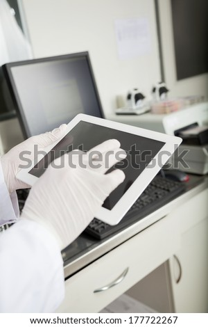 Cropped image of male researcher using tablet computer in medical lab - stock photo