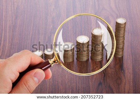 Cropped image of man analyzing coin stacks with magnifying glass - stock photo