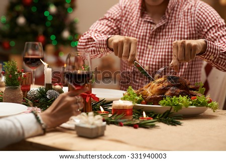Cropped image of man cutting roasted chicken at the Christmas family dinner - stock photo