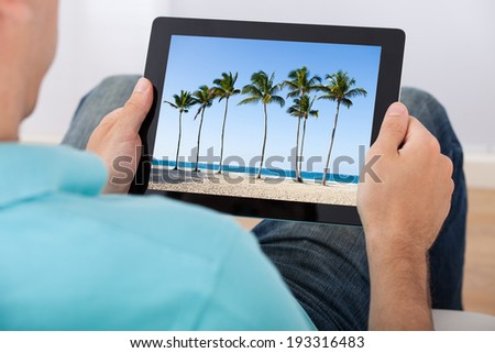 Cropped image of man looking at beach photo on tablet - stock photo